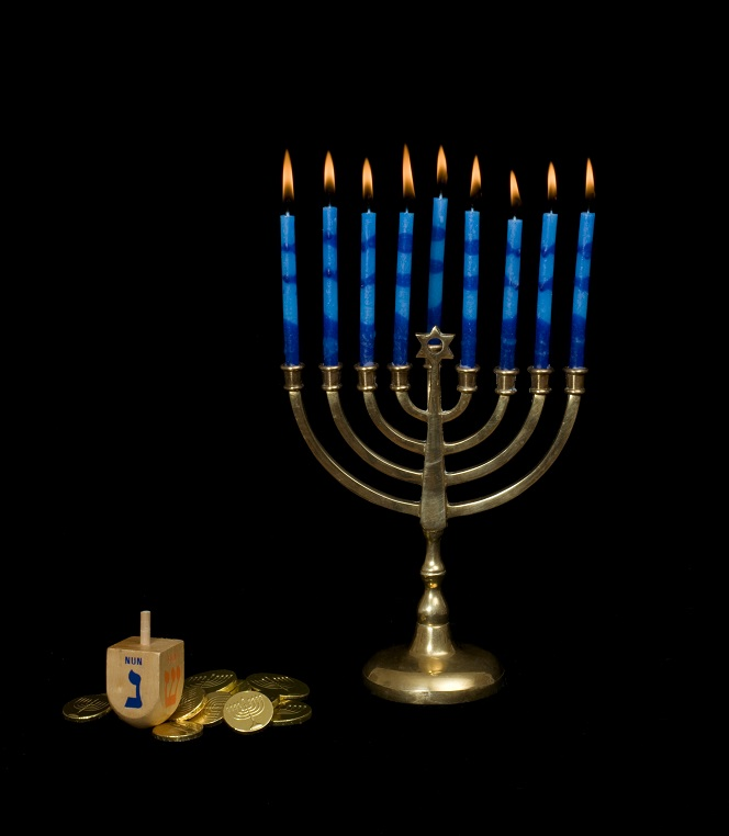 Lighted Hanukkah menorah with a dreidel and gelt at the base set against a black background.